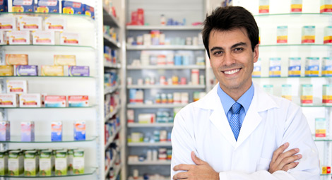 A pharmacist stood behind his counter with his arms folded staring out to the camera